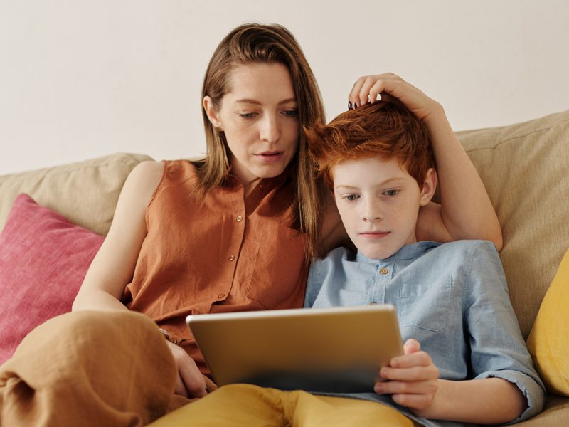 Woman and boy watching tablet computer