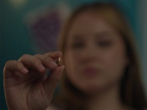 Hannah holds the bullet that killed her best friend. She was shot by the same bullet which ended up in her ribcage.